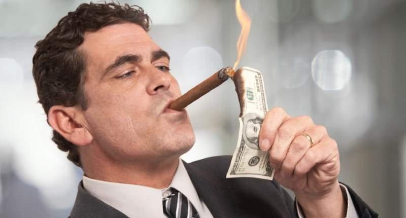 Businessman-lighting-cigar-with-100-dollar-bill