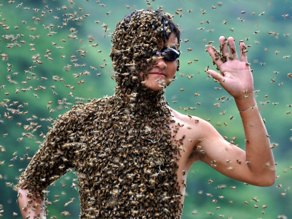 Beekeeper Lv Kongjiang, 20, waves as he stands with bees partially covering his body on a weighing scale during a Reuters